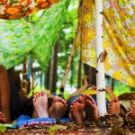 Kids feet sticking out of makeshift fort in the woods.