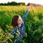 A little girl runs through a meadow wiht the sun on her back.