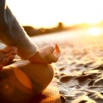 A woman does yoga on the beach at sunset.