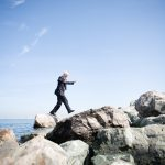 Sirna Therapeutics executive leaps from one rock to another outside the corporate offices in San Francisco.