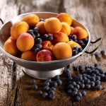 Colander of apricots and blueberries