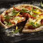 Peppers and pepperoni rocket pizza with slice cut